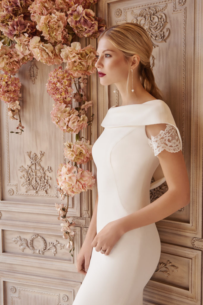 Our unique dress Rieko is designed and made using a crepe silk, through our made to measure service. Pairing it with a delicate lace around the sleeve and train, in a fitted style we have been able to create a modern take on a classic shape. Finally, having a soft open scoop neck and low back we are allowing the light to capture the essence of the wearer and highlight her best features.